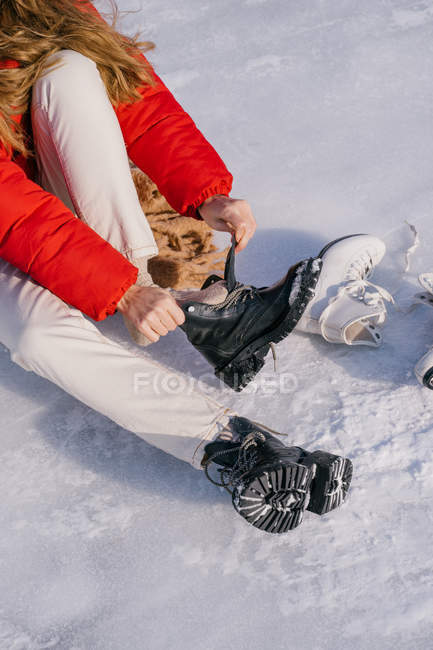 Cropped image of woman in warm sportswear sitting and putting on black boots with grooved sole during trip in Siberia — Stock Photo
