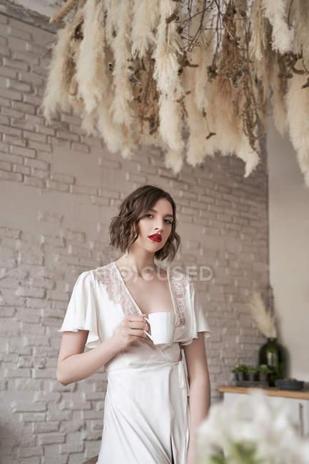 Nachdenkliche Frau schaut weg und überlegt beim Heißgetränk in der Küche — Stockfoto