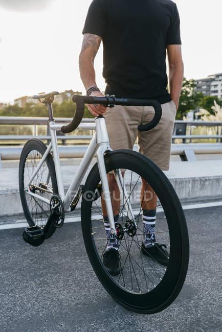 Перекручений образ велосипедиста в спортивному лаві стоїть з велосипедом на мості. — стокове фото