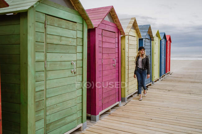 Trendy woman in black cap and leather jacket walking pass wooden beach cabin — Stock Photo