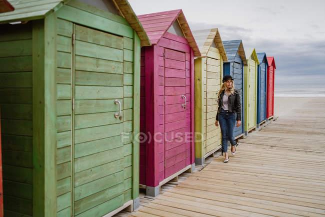 Une femme à la mode portant une casquette noire et une veste de cuir passe la cabine de plage en bois — Photo de stock