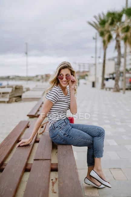 Une jolie femme avec un beau sourire en chemise à rayures décontractées regarde la caméra au-dessus de lunettes de soleil à la mode — Photo de stock