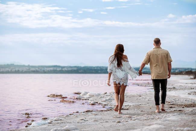 Rückansicht eines Paares, das auf einem fantastischen rosafarbenen See aus Meerwasser und blauem Himmel Händchen haltend spaziert — Stockfoto
