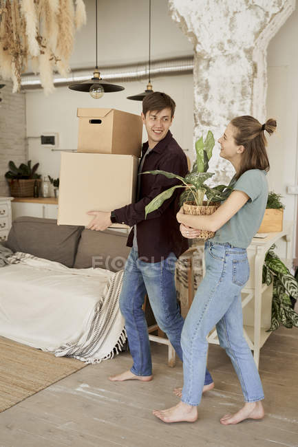 Barefoot woman carrying pot with flower and looking at man carrying boxes — Stock Photo