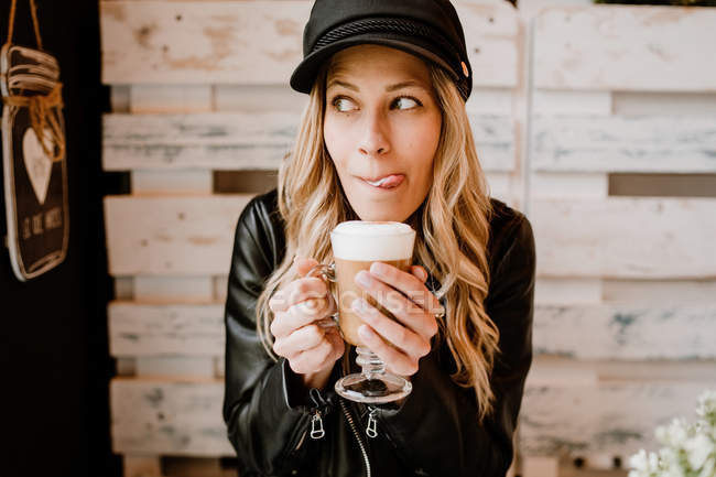 Long haired trendy woman holding glass of delicious foamy coffee, licking lips in cafe — Stock Photo