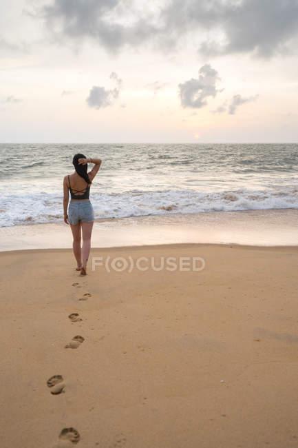 Женщина в камуфляже ходит по песчаной колее — стоковое фото