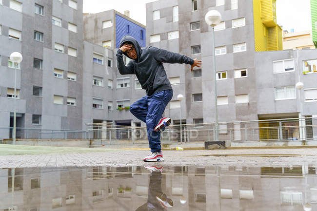 From below of young guy in street style clothing dancing outdoors with buildings on background on rainy day — Stock Photo