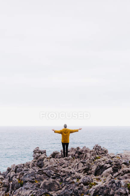 Back view of woman in yellow hoodie stepping on stony shore surrounded by foamy waves on gray cloudy day — Stock Photo