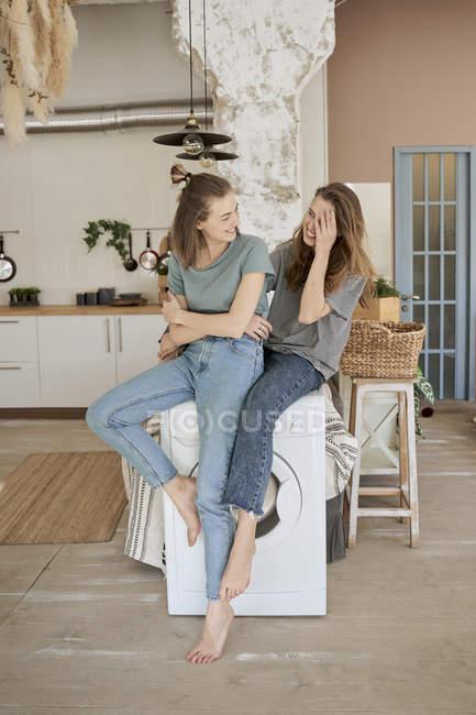Веселые случайные женщины смеются и сидят на белой стиральной машине в просторной кухне, веселясь дома — стоковое фото