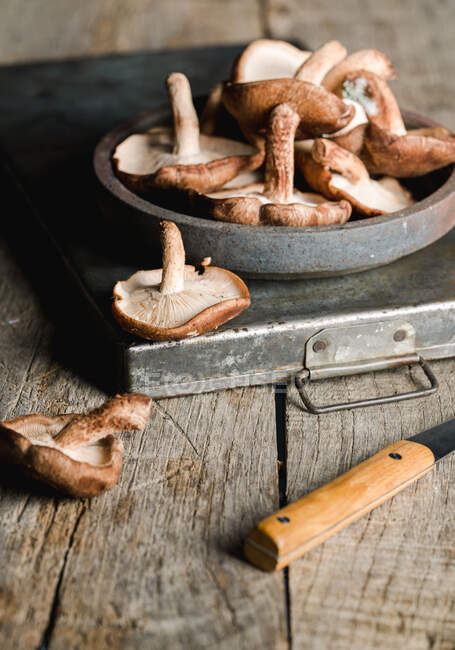 Pile of fresh brown mushrooms on rustic wooden table — Stock Photo