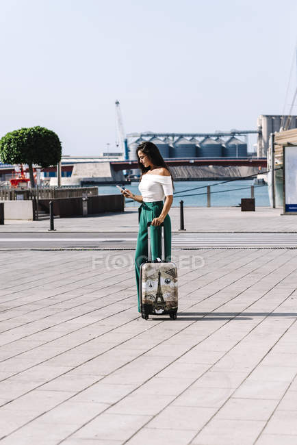 Side view of stylish young woman on the mobile phone with suitcase standing on the street — Stock Photo