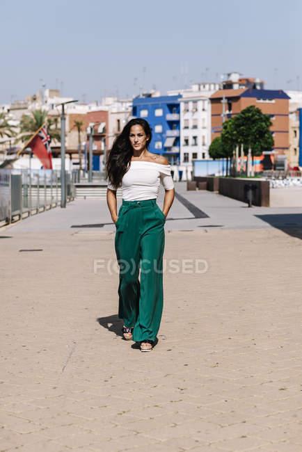 Stylish woman walking on street hands on pocket — Stock Photo