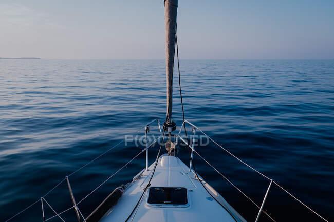 Vista dal ponte della barca a vela che scorre sull'acqua calmata del mare al tramonto — Foto stock