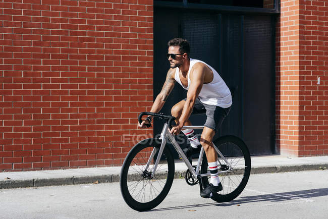 Modern male cyclist in sportswear and sunglasses riding a bicycle near red brick wall — Stock Photo