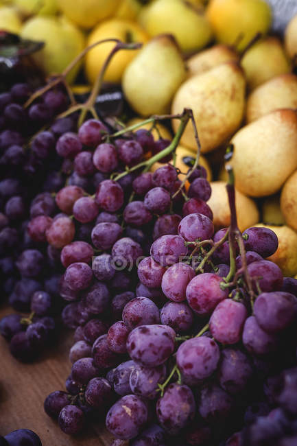 Stand full of ripe organic grapes and pears at farmers outdoor market — Fotografia de Stock