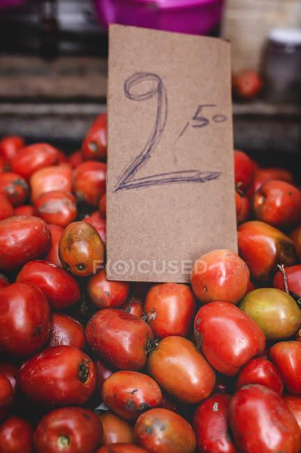 Stand voller reifer Bio-Tomaten mit Preisschild auf Bauernmarkt — Stockfoto