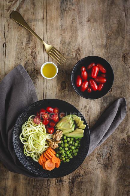 Macarrão vegan cru de abobrinha com ervilhas, tomates cereja, abacate, cenouras, nozes e azeite em tigela servida em fundo de madeira — Fotografia de Stock