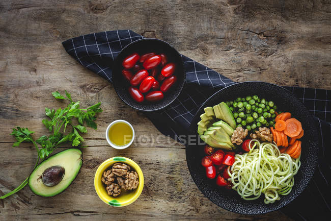 Zucchini raw vegan pasta with peas, cherry tomatoes, avocado, carrots,nuts and olive oil in bowl served on wooden background — Stockfoto