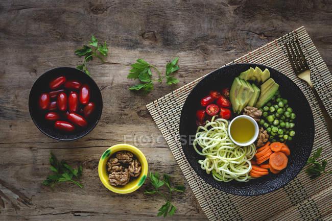 Zucchini rohe vegane Pasta mit Erbsen, Kirschtomaten, Avocado, Karotten, Nüssen und Olivenöl in einer Schüssel auf Holzboden serviert — Stockfoto