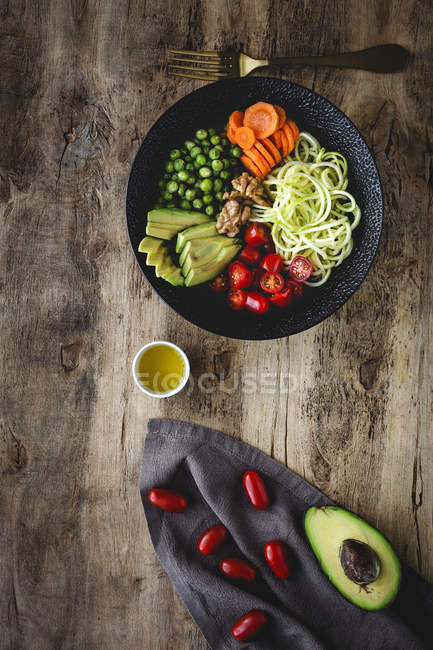 Zucchini raw vegan pasta with peas, cherry tomatoes, avocado, carrots,nuts and olive oil in bowl served on wooden background — стоковое фото