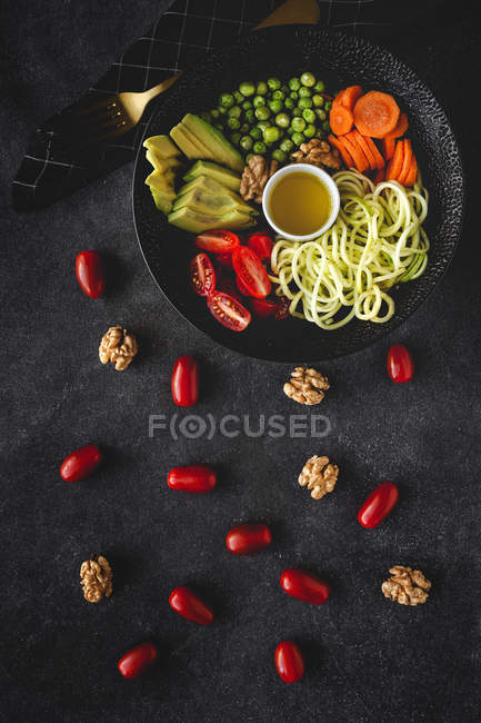 Zucchini raw vegan pasta with peas, cherry tomatoes, avocado, carrots,nuts and olive oil in bowl served on dark background — Stock Photo