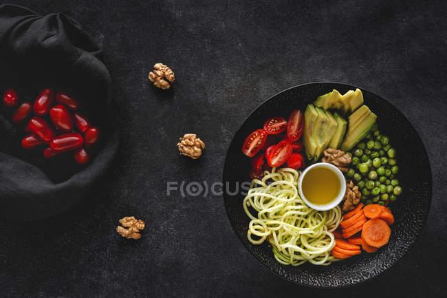 Zucchini rohe vegane Pasta mit Erbsen, Kirschtomaten, Avocado, Karotten, Nüssen und Olivenöl in einer Schüssel auf dunklem Hintergrund serviert — Stockfoto