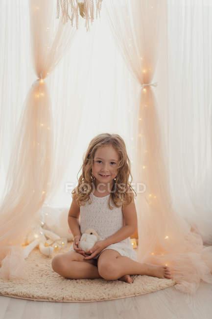 Tenera bambina in abito bianco seduta su tappeto con giocattolo, sorridente e guardando in macchina fotografica da luci fatate e tendaggi alla moda — Foto stock