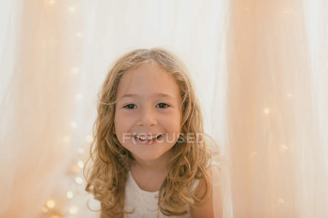 Tender little girl in white dress sitting smiling and looking in camera by fairy lights and stylish draperies — Stock Photo