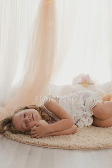 Нежная маленькая девочка в белом платье лежит с закрытыми глазами на ковре, обнимая игрушку от волшебных огней и стильных драпировок — стоковое фото