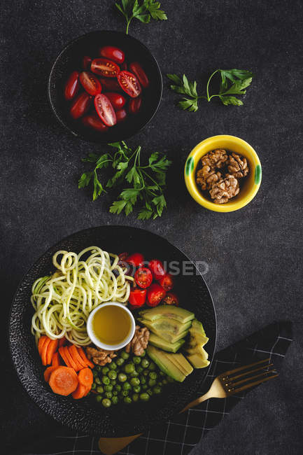 Zucchini raw vegan pasta with peas, cherry tomatoes, avocado, carrots,nuts and olive oil in bowl served on dark background — Stockfoto