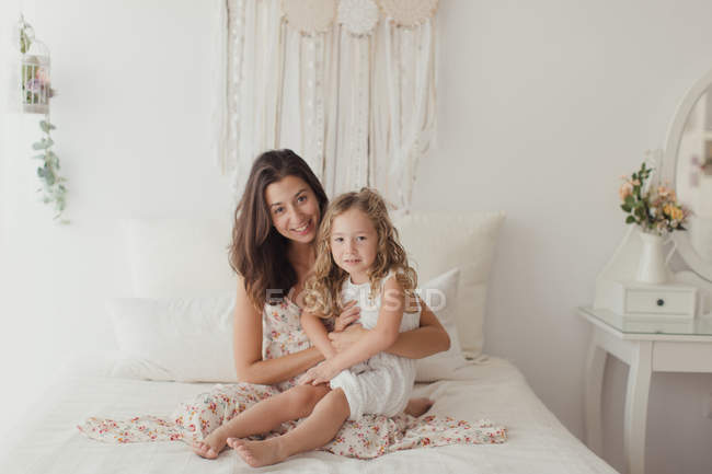 Happy brunette mother having fun with blonde cute daughter while embracing on bed — Stock Photo