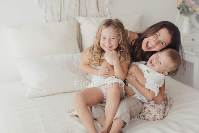 Positive young brunette sitting on bed and hugging little male and female children while looking in camera at stylish bedroom — Stock Photo