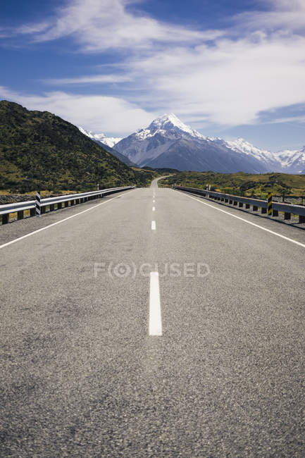 Asphalt road and tropical green cliffs and blue lake with cloudy blue sky and Mountain Cook in New Zealand — Stock Photo