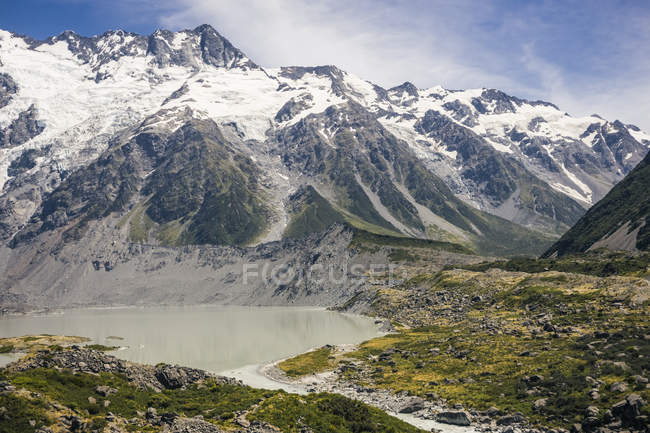 Powerful overgrown cliffs near small lake and big snowy mountain Cook with blue skyline at New Zealand — Stock Photo