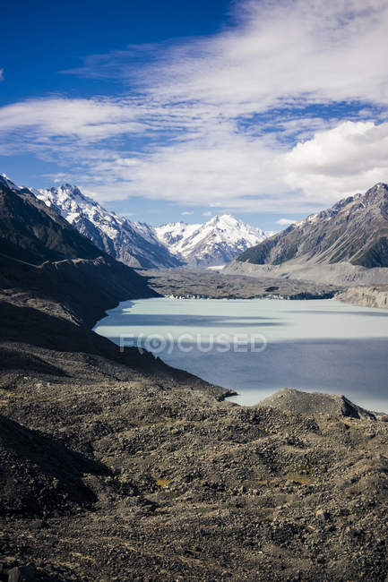 Rocky coast of lake with blue sky and mountain Cook at New Zealand — Stock Photo
