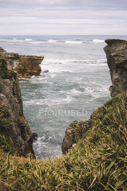 From above of rocky overgrown of plants seashore with waves and cloudy sky in Pancake Rocks in New Zealand — Stock Photo