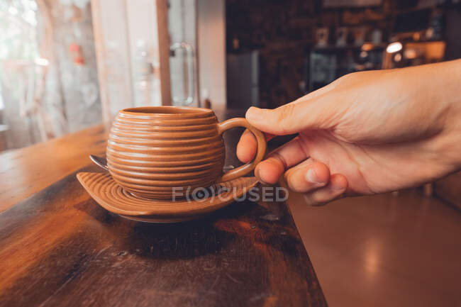 Crop person holding cup of coffee on table — Stock Photo