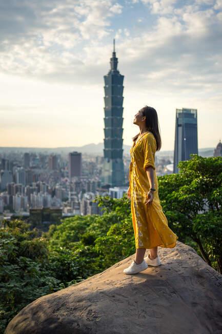 Молода жінка, яка відпочиває, захоплюючись краєвидами у великому місті. — стокове фото