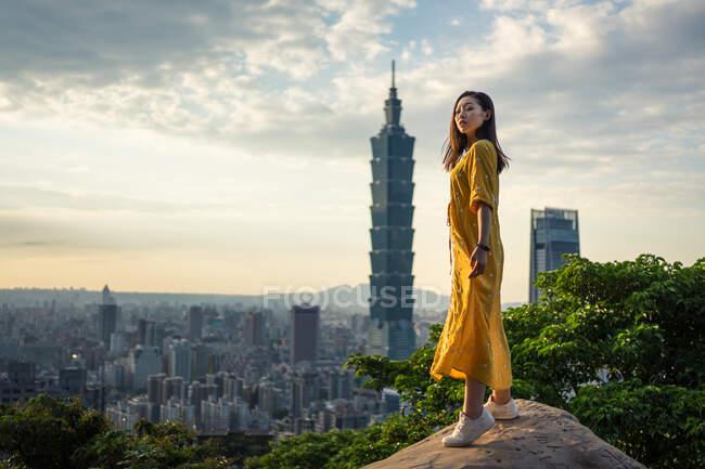 Joven dama descansando deleitándose con las vistas en roca en la gran ciudad - foto de stock