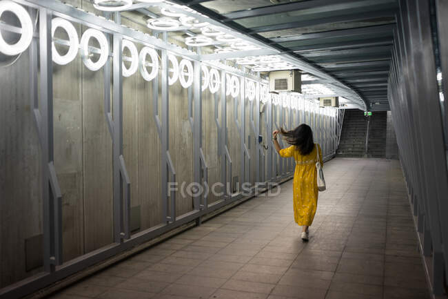 Back view of female traveler in stylish yellow gown walking while fixing black hair at modern on subway at Scotland — Stock Photo