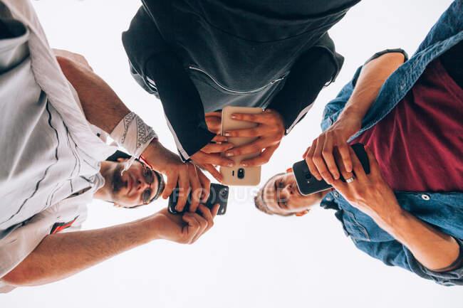 Desde abajo de los jóvenes hipsters en ropa casual de pie y formando un anillo mientras navega por los teléfonos móviles sobre fondo blanco - foto de stock