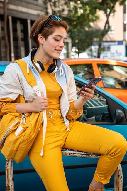 Adolescente moderno con cuffie e borsa surf cellulare mentre seduto contro auto colorate ed edifici moderni — Foto stock