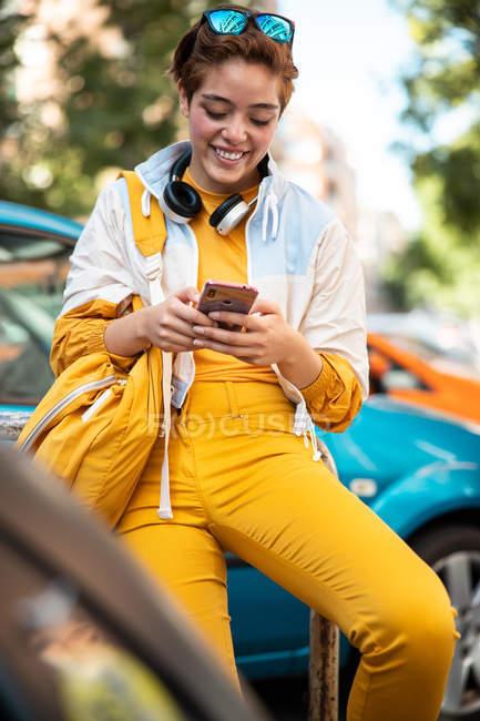 Moderner Teenager mit Kopfhörern und Handtasche surft im Sitzen gegen bunte Autos — Stockfoto
