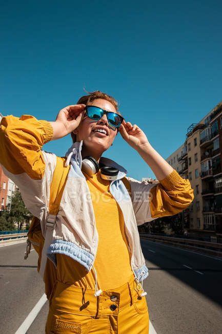 Low angle millennial female in sunglasses and vivid white and yellow outfit wearing headphones against blurred city street — Stock Photo