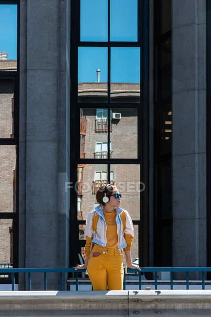 Тендітна щаслива жінка в навушниках і жовтий одяг з рюкзаком стоячи проти вікна фасаду з віддзеркаленням — стокове фото