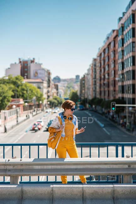 Femme en vêtements blancs et jaunes avec sac à dos debout sur le pont et regardant le téléphone portable contre la rue et les bâtiments — Photo de stock