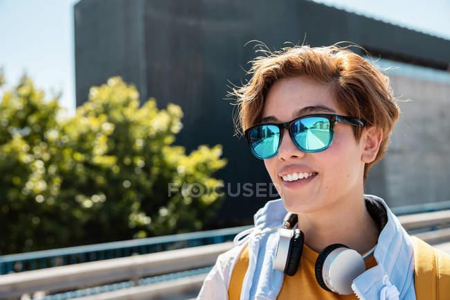 Una hembra milenaria llena de gafas de sol que disfruta de vistas a la calle de la ciudad. - foto de stock