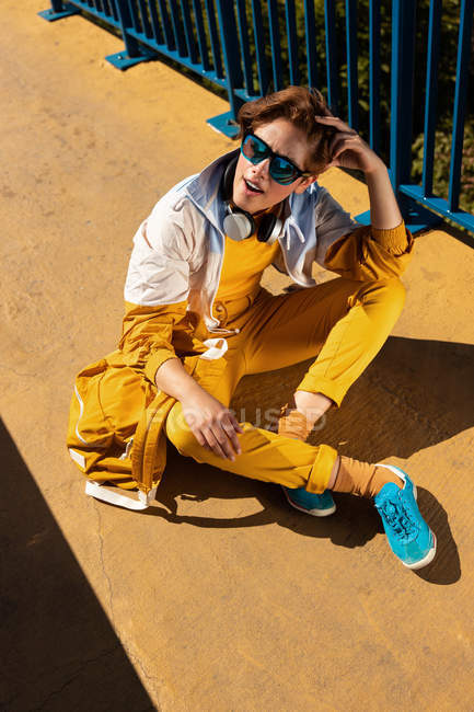 From above chilling teen in sunglasses listening to music with headphones while sitting on vivid pavement with blue fence — Stock Photo