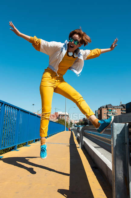 From below cheerful courageous teenager in sunglasses jumping with mouth open and arms raised on street — Stock Photo