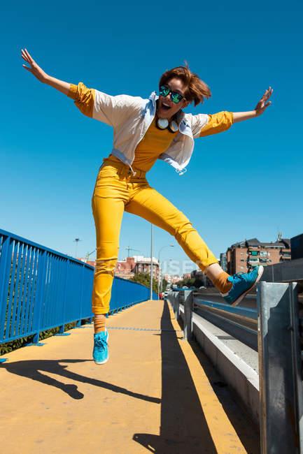 D'en bas courageux adolescent joyeux dans des lunettes de soleil sautant avec la bouche ouverte et les bras levés dans la rue — Photo de stock